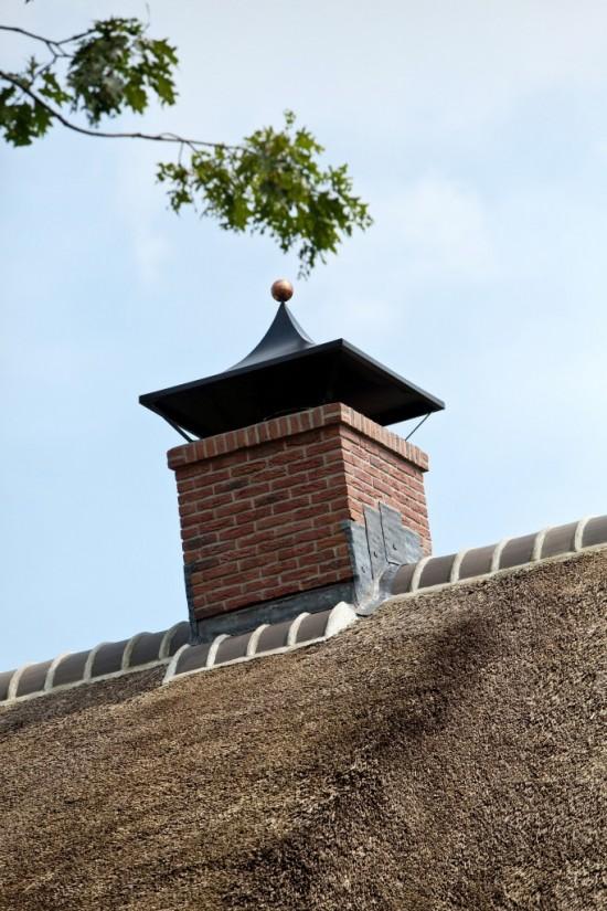 13. Rietgedekt huis bouwen Stenen schoorsteen met stalen kap Ugchelen